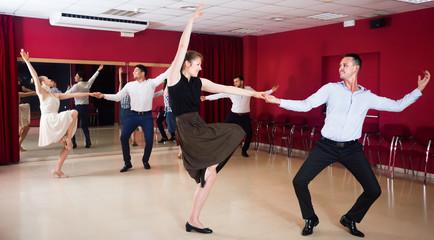 Cheerful people dancing lindy hop in pairs