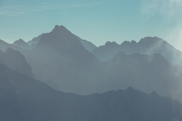 Mountain peaks in Tatra mountains and fog. Photography in pastel colors.
