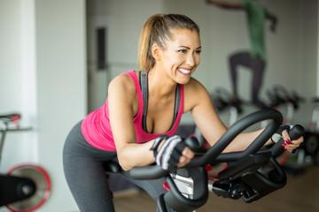Beautiful young woman doing cardio on a stationary bike