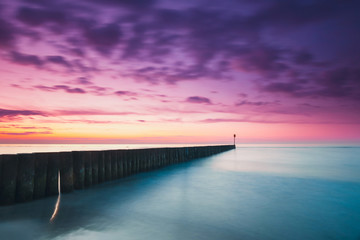 Acrylic Prints Eggplant Sunset on the beach with a wooden breakwater, purple tone