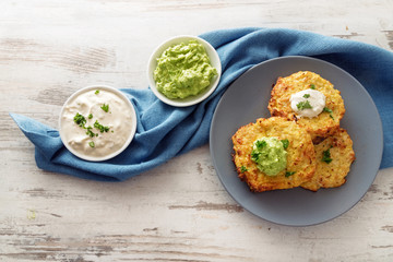 vegetable rosti from cauliflower and parmesan with two dips from sour cream and avocado, parsley garnish, blue plate and napkin on a bright wooden table with copy space, high angle view from above