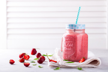 Strawberry smoothie or milkshake in jar with fresh mint.Healthy food for breakfast and snack.Super Food.Copy space for Text. selective focus.