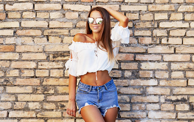 Street photo of sensual stylish girl in jeans shorts and sunglasses