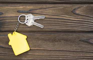 keys to housing with a keychain in the form of a house on a wooden background. the property. purchase of housing. mortgage.