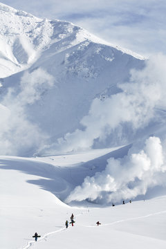 Snowboarders hiking on snow covered mountains