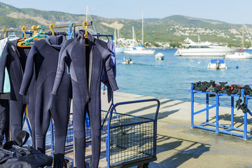 diving suits hanging to dry on the background of the Mediterranean sea and the mountains