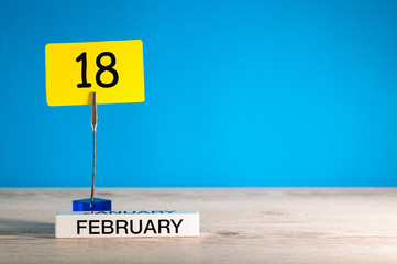 February 18th. Day 18 of february month, calendar on little tag at blue background. Winter time. Empty space for text, mockup