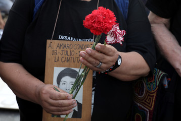 Raida Condor holds a picture of her son Amaro Condor as relatives of victims of the guerrilla conflict in the 80s and 90s protest against pardoning of former president Alberto Fujimori, in Lima, Peru