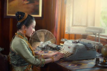 The girl uses a typewriter and a desk lamp. Business concept, retro style image with a costume in Laos.