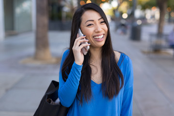 Young Asian woman walking street talking cell phone