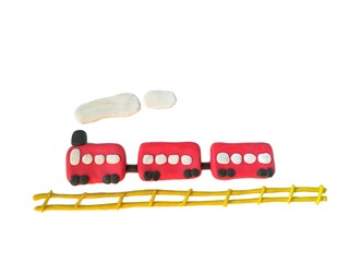 Plasticine clay made are cute red train running on the yellow railway placed on white background