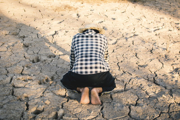 Asian man on cracked dry ground, concept drought and crisis environment