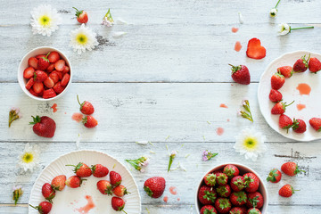 Top view of fresh strawberry in bowls and on plates decorated with flowers on white table with copy space.