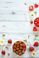 Top view of fresh strawberry in bowl decorated with flowers on white table with copy space.