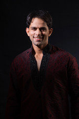 portrait of young male indian model, isolated over black background highlighting face, indian model posing in ethnic clothing