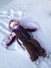 Cute little Toddler kid girl in colorful pink and brown  winter clothes making snow angel, laying down on snow. Active outdoors leisure with children in winter. Happy child