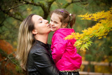 Beautiful Young Mother Showing Leaves to Four Years Old Cute Toddler Girl in Japanese Park in Portland Oregon USA, Portrait Close-up, Happy Family Concept, Colorful Fall Colors