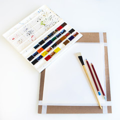 Board for drawing with brushes, paper and pencil on a white background.