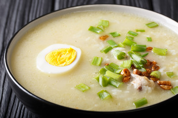 Arroz Caldo rice soup with chicken, garlic, onion and egg close-up. horizontal
