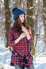 In winter, the girl is posing in a blue cap, a checkered red-and-black shirt.