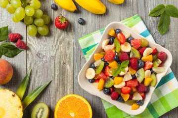 Delicious fruit salad with fresh fruit. Wooden, gray table in the background.