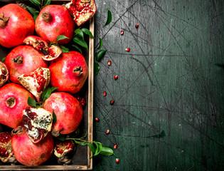 Fresh pomegranates on a wooden tray.