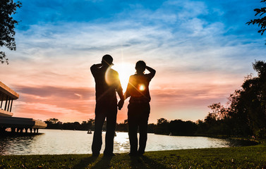 The silhouette of the couple is holding hands and looking at the colorful sunset together.