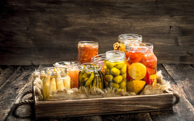 Different preserved vegetables from vegetables and mushrooms in glass jars.