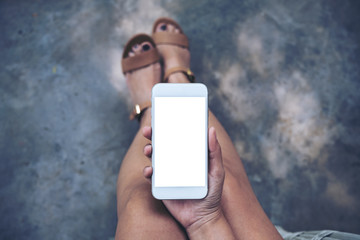 Top view mockup image of a woman sitting and holding white mobile phone with blank desktop screen