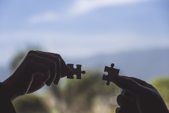 Closeup image of two hands holding a jigsaw puzzle with feeling love