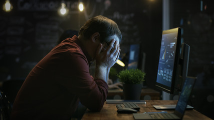 Stressed Financier Hits the Table with His Fist in Frustration and Covers His Face in Hands. He's Working on a Personal Computer with Statistics Showing on the Screen.