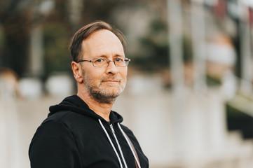 Outdoor portrait of 50 year old man wearing black hoody and eyeglasses