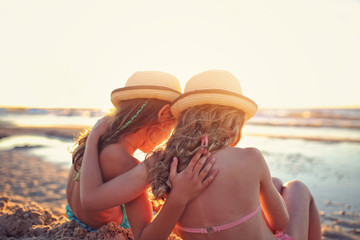 Two young girls talk  and have fun on the beach