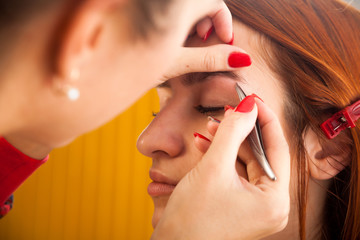 Close up of the master on the eyebrows corrects the shape of the roach with tweezers  red-haired beautiful woman on a white background; view from above