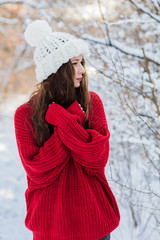 On a winter sunny day, a young girl with long hair poses in a white hat and a red sweater. Cold.