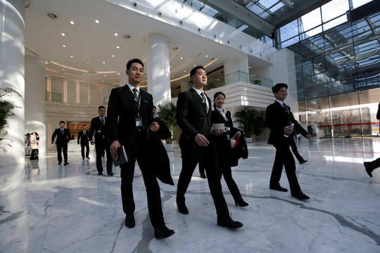 Members of JD.com's VIP delivery team leave the company headquarters building after a training on business etiquette in Beijing