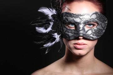 Frau mit Federn Maske blickt cool