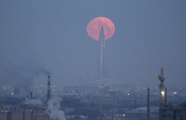 A full moon is seen behind the business tower Lakhta Centre in St. Petersburg