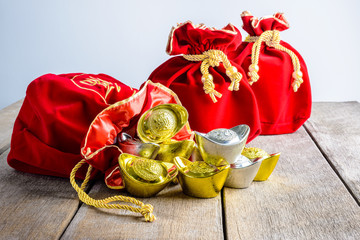 Chinese New Year Red fabric bag, ang pow with Chinese money of luck and Shoe-shaped gold ingot