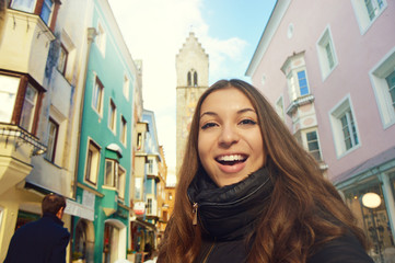 Happy smiling girl in front of Zwölferturm tower in the old town of Sterzing, South Tyrol, Italy. Beautiful young woman winter travel in Europe.