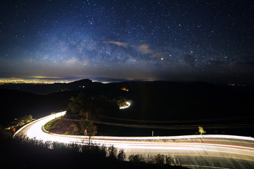 Milky way galaxy with stars and space dust in the universe and lighting on the road at Doi inthanon Chiang mai, Thailand