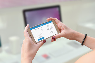 Woman holding smart phone and watch crypto currency stats. Office computer in background.