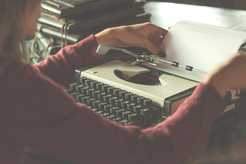 Woman writing on the vintage typing-machine. Shallow depth of field on keyboards.