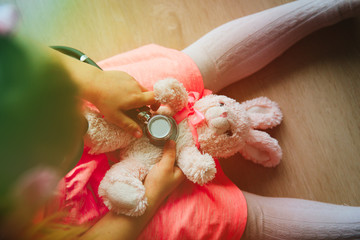 little girl play doctor or nurse with toy, listen to stetoscope