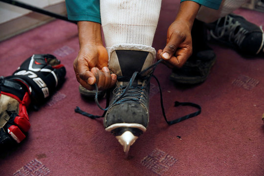 Member of Kenya's ice hockey team puts on his skates before a practice session in East Africa's only ice rink, in Nairobi