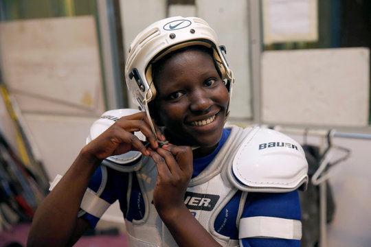 Female member of the Kenya's ice hockey team gears up before a practice session in East Africa's only ice rink, in Nairobi