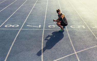 Sprinter sitting on running track