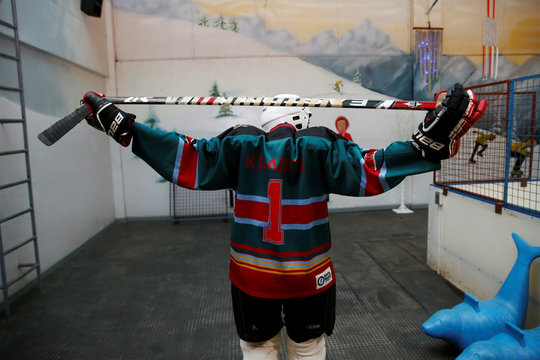 Member of Kenya's ice hockey team stretches before a practice session in East Africa's only ice rink, in Nairobi