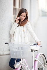 Young woman standing next to her bicycle and talking on the phone