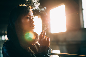 Young woman smoking marijuana in abandoned industrial building